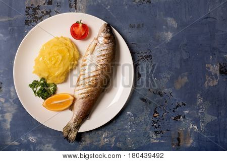 Grilled whole trout, mashed potato, lemon and parsley, top view