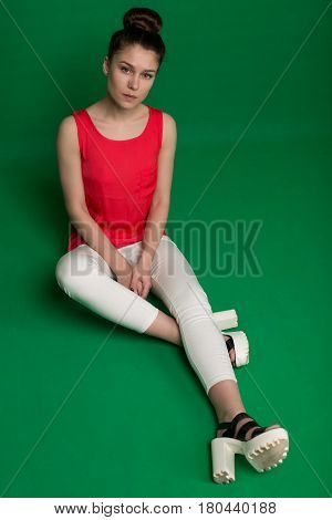 Beautiful Young Girl In A Red Blouse And White Trousers On A Green Background