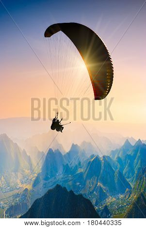 Paraglide silhouette over mountain peaks in a sunset light.