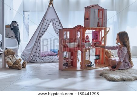 Playing with her toys. Cute little girl playing with a dollhouse while sitting on the floor in bedroom
