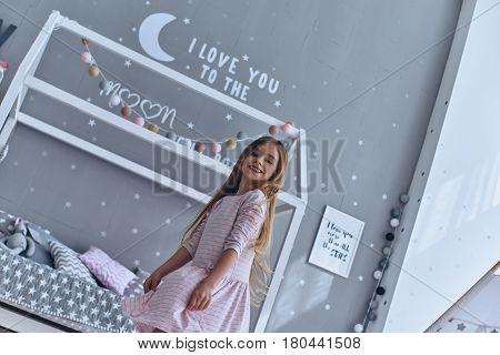 Playful girl. Lovely little girl smiling and looking at camera while standing in bedroom