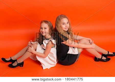 Two Sisters In Beautiful Stylized Dresses On A Red Background In The Studio