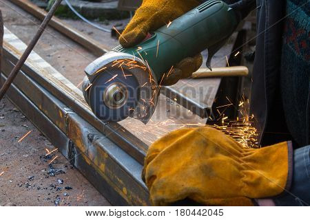 Cutting metal with grinder. Sparks while grinding iron. Man in yellow gloves