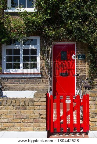 LONDON, UK - MAY 09, 2016: Red door and wooden gate of a traditional English house.