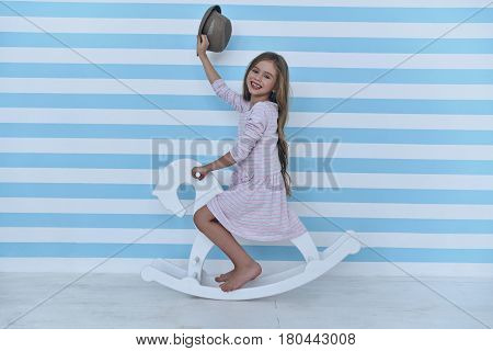 On the way to her dreamland. Cute little girl waving with her hat and looking at camera with smile while sitting on the toy horse
