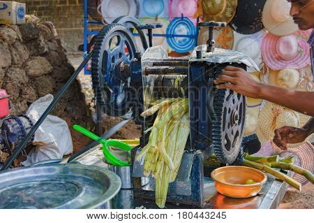 Goa, India - November 13, 2012: Young man cooking and selling India's popular street reed juice. The traditional method of preparation of the drink. Motion blur.