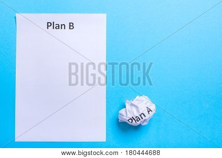 Crumpled paper Plan A and clean sheet Plan B on a blue background