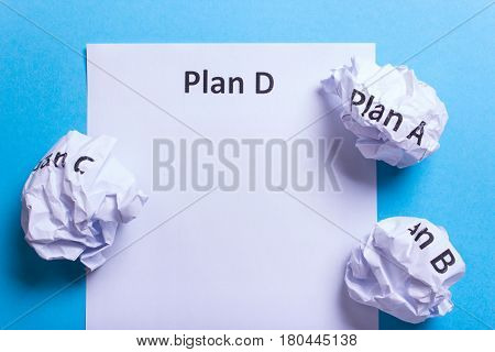 Crumpled paper Plan A B C and clean sheet Plan D on a blue background