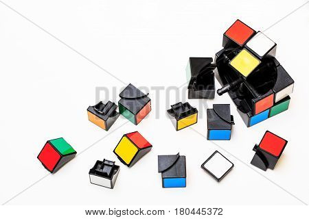 Vladivostok Russia - March 11th 2017: Vladivostok the broken cube of Rubiks with the parts scattered from it on the isolated background.