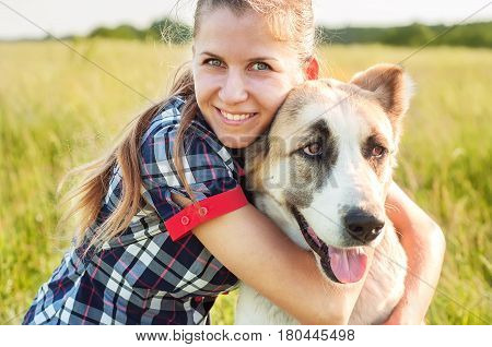 Girl and dog Central Asian Shepherd hug in a park. Walking with a pet. Pedigree dog. Walking dogs. Dog happiness.