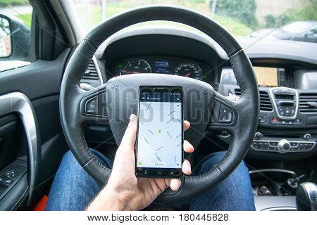 Nitra, Slovakia, april 7, 2017: Driver holding smartphone with Here we go maps application behind the driving wheel in car