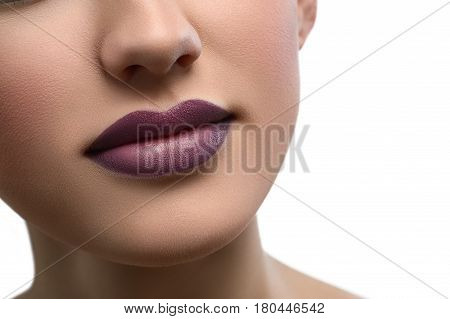 Close up shot of a beautiful smile of a woman with full sexy lips covered with purple lipstick isolated copyspace beauty fashion skin unblemished augmentation fillers cosmetology makeup visage .