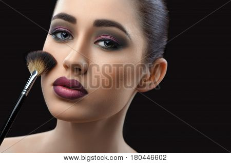 Cropped close up of a gorgeous dark haired fashion model with evening makeup posing sensually holding blush brush on dark background copyspace beauty fashion industry cosmetics lipstick concept.