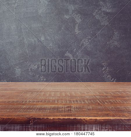 Empty wooden table over dark blackboard background for product montage display
