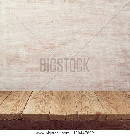 Empty wooden board table over painted white wall background for product montage display
