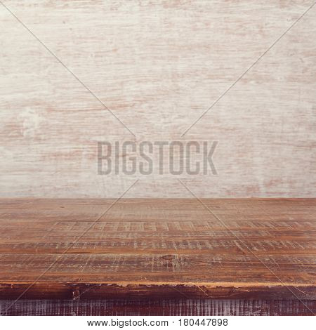 Empty wooden table over painted white wall background for product montage display