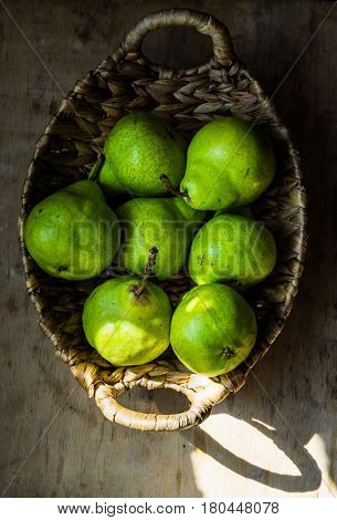 Ripe green organic pears in vintage wicker basket on weathered wood kitchen table sunlight flecks top view