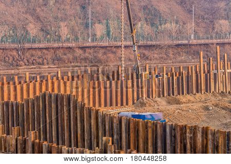 Construction site surrounded by wall of vertical metal beans with industrial drilling machine behind far wall with river and trees in background