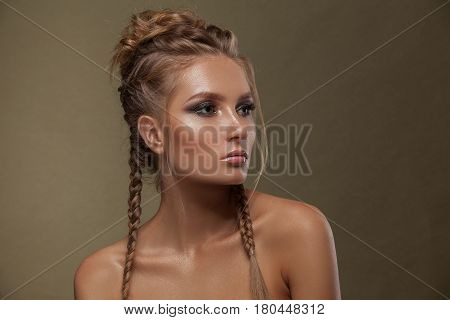 Beauty female model with beautiful make-up of color and haircut from pigtails. Brown hair braids of hair clean shiny skin a face of beauty. Glamorous portrait shot in studio on a green background.