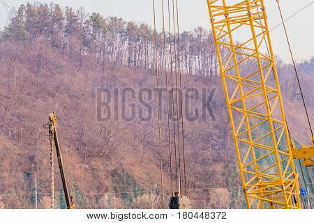 Yellow industrial crane and drilling machine at construction site with trees and brush on the side of a hill in the background