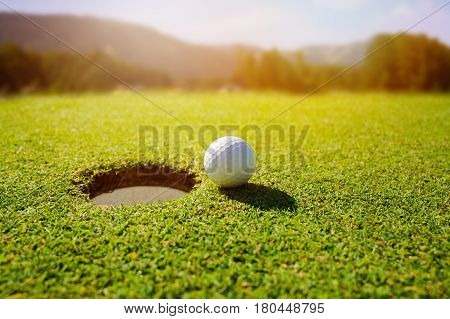 Golf ball on lip of hole over beautiful green loan