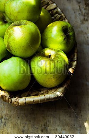 Green ripe organic bio apples local produce in rustic wicker basket on weathered wood table harvest autumn cozy atmosphere copyspace