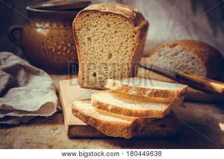 Sourdough bread loaf sliced on old wood cutting board vintage crockery linen towel authentic rural style still life toned