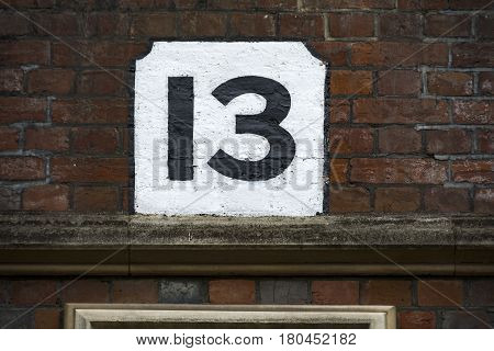 Number thirteen hand painted on plaster background