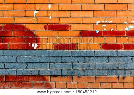 Brick wall painted blue and red paint with traces of ads. Abstract background