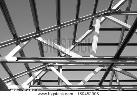 Black and white photoStructure of steel roof frame for building construction.