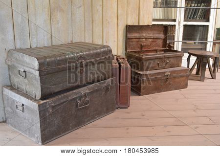 Old scrap boxes on a wooden floor with a suitcase