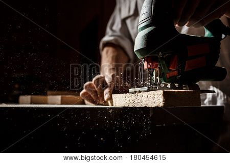 Close up photo of cutting wood with fretsaw over dark background. Copy space.