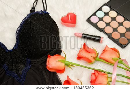 Part of the black lace bodice. Orange roses lipstick and eye shadow. Fashionable concept. Top view