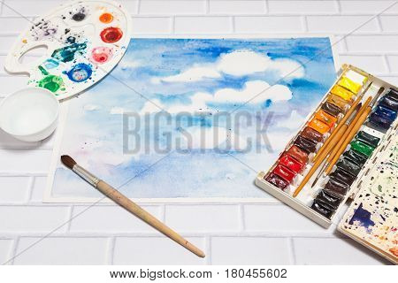 Hand drawn Sketch of Bright Colorful Blue Sky With White Clouds, with lying flat paints, paintbrushes and palette on the white brick background - tools for drawing, perspective view