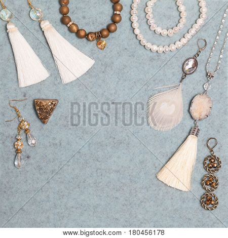 Handmade set of white, golden, bronze, ivory bijouterie with gems, tassels, cryslals and feathers, lying on the gray wool background, top flat view with empty place for your text