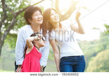Portrait of happy multi generations Asian family at park. Grandmother, mother and daughter outdoor fun, exploring the nature. Morning sun flare background.