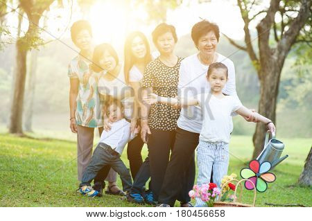 Large group of happy Asian multi generations family playing at park, grandparent, parent and children, outdoor nature park in morning with sun flare.