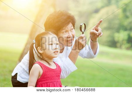 Portrait of beautiful multi generations Asian family at nature park. Grandmother and granddaughter having fun at outdoor. Morning sun flare background.