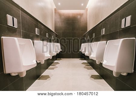 Urinals in men's public modern toilet restroom sanitary or wc architecture design concept