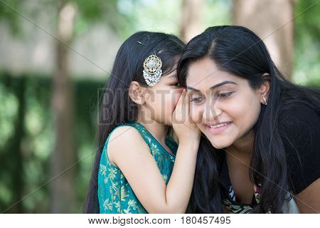 Closeup portrait daughter whispering secrets in mom's ear isolated outdoors outside green trees background