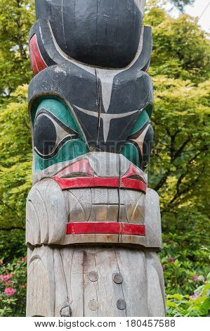 Colorful Inuit totem poles in Forsest of Canada or Alaska