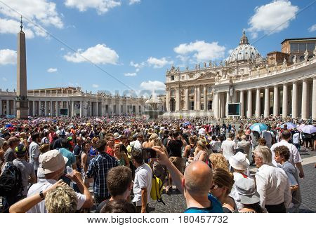 VATICAN CITY ITALY - July 26 2015: A large crowd gathered in St. Peter's Square. Admission to the Chapel and Museums is free on the last Sunday of the month drawing large crowds who also hear the Papal address and receive the Pope's blessing.