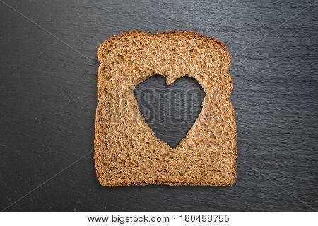 Whole Grain Sandwich Bread Slice With Heart Cut Shape, On Dark Surface/background.
