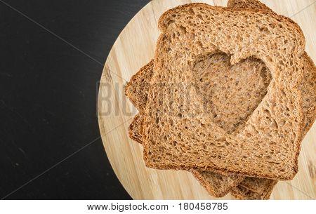 Whole Grain Sandwich Bread Slices With Heart Cut Shape, On Wooden Plate