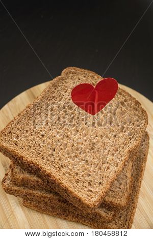 Whole Grain Sandwich Bread Slice With Heart Pin, With Dark Background.