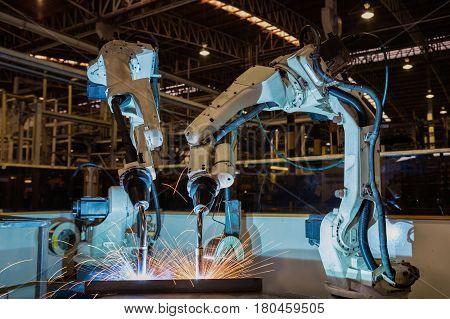 Team robots are test run welding in  factory
