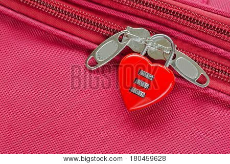 Closeup top view of red heart shaped lock with code locking fabric suitcase luggage