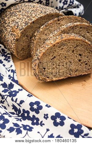 Whole Wheat Sliced Bread Closeup , On Wooden Surface With Floral Kitchen Towel.