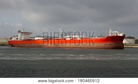 Red oil tanker moored at an oil terminal in the Port of Rotterdam.