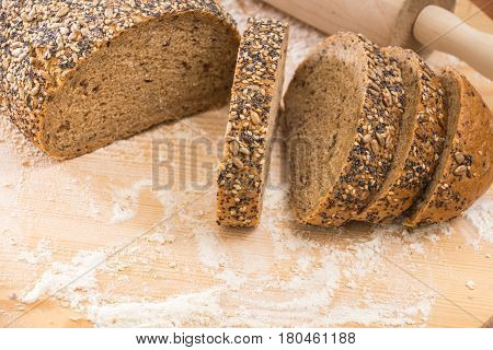 Whole Wheat Sliced Bread Closeup, On Wooden Surface With Flour.